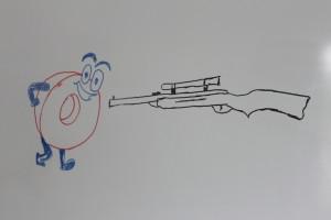 Null mit Augen, Händen und Füßen (ähnlich die der kleinen Preise von Plus) läuft auf ein Luftgewehr mit Zielfernrohr zu, zum Skatspruch Null ans Gewehr